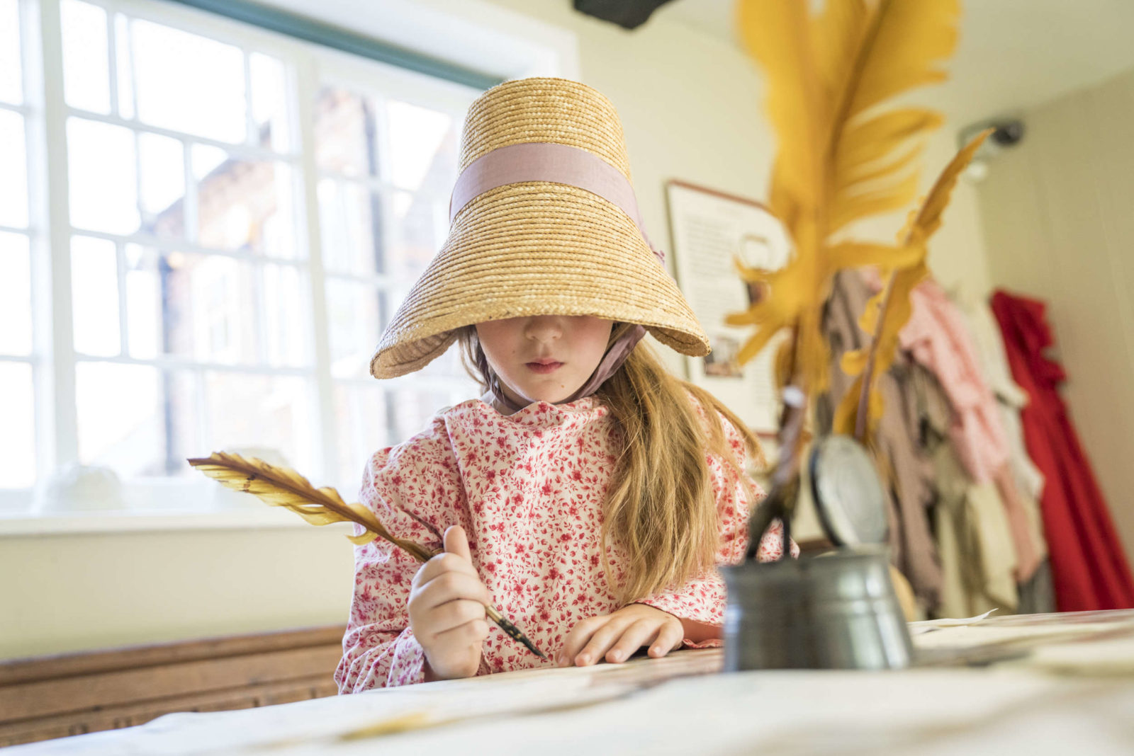 A young girl in a bonnet writing with a quill pen at Jane Austen's House