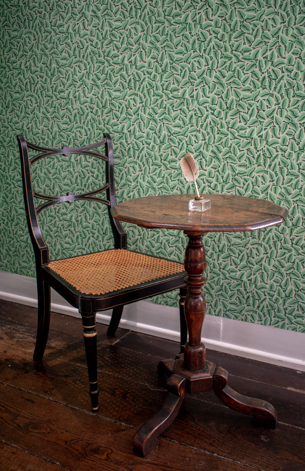 Jane Austen's writing table set against the Chawton Leaf wallpaper in the Dining Parlour