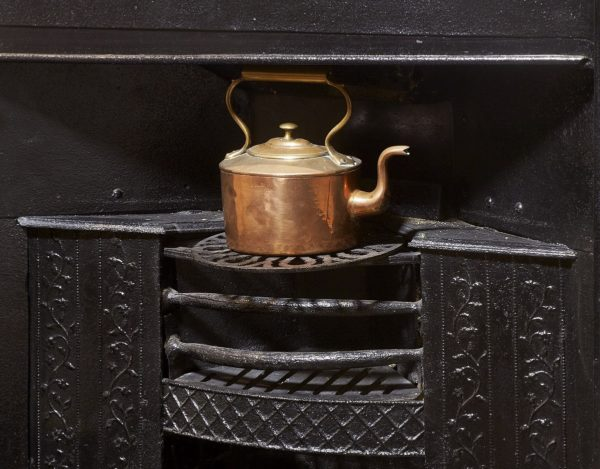 Black iron grate in the Dining Parlour at Jane Austen's House, shown with copper kettle