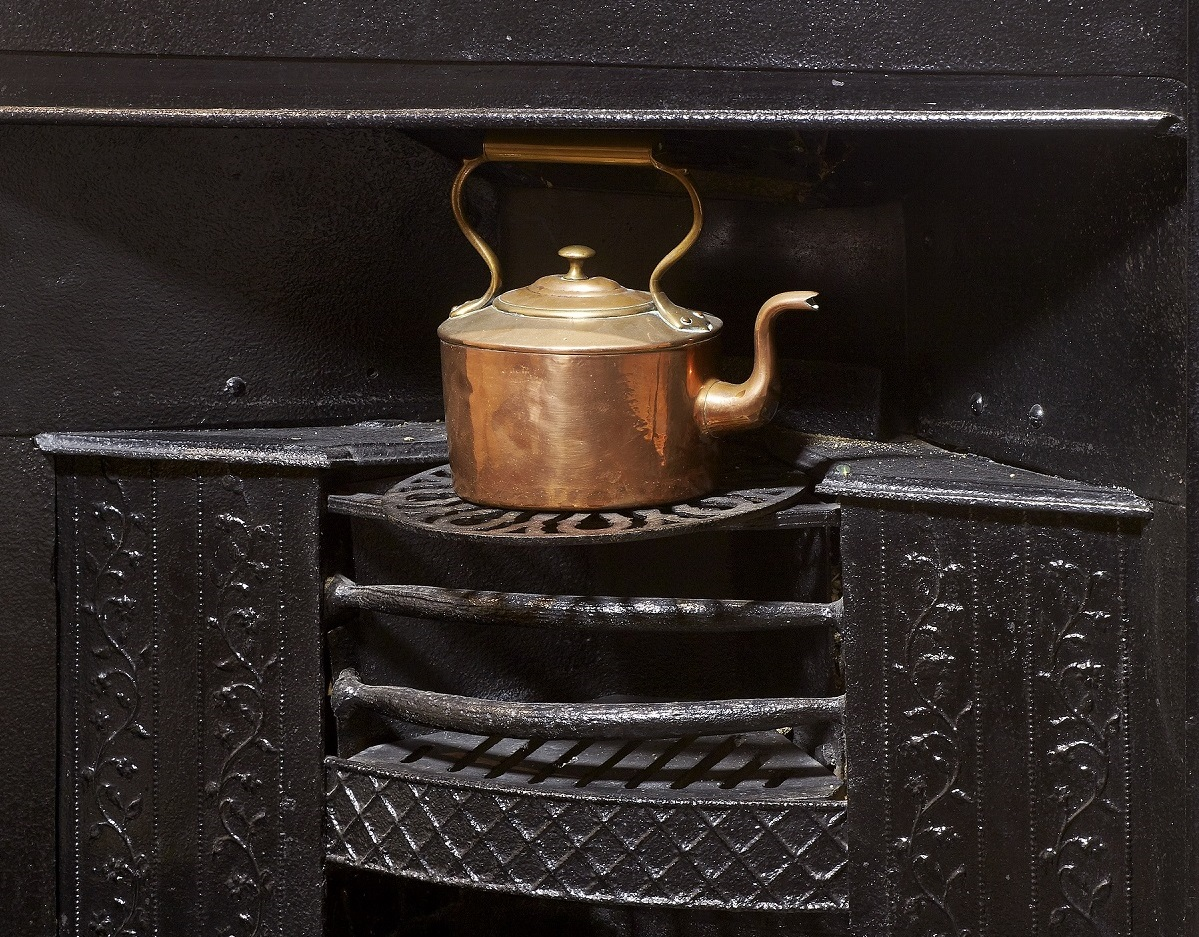 Black iron grate in the Dining Room at Jane Austen's House, shown with copper kettle