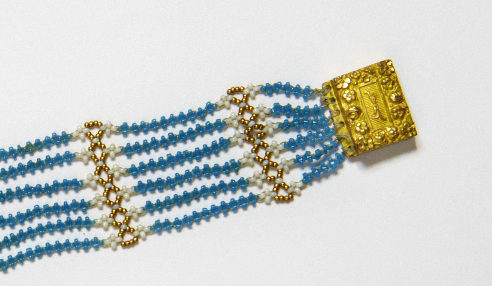 Close up of Jane Austen's blue bead bracelet