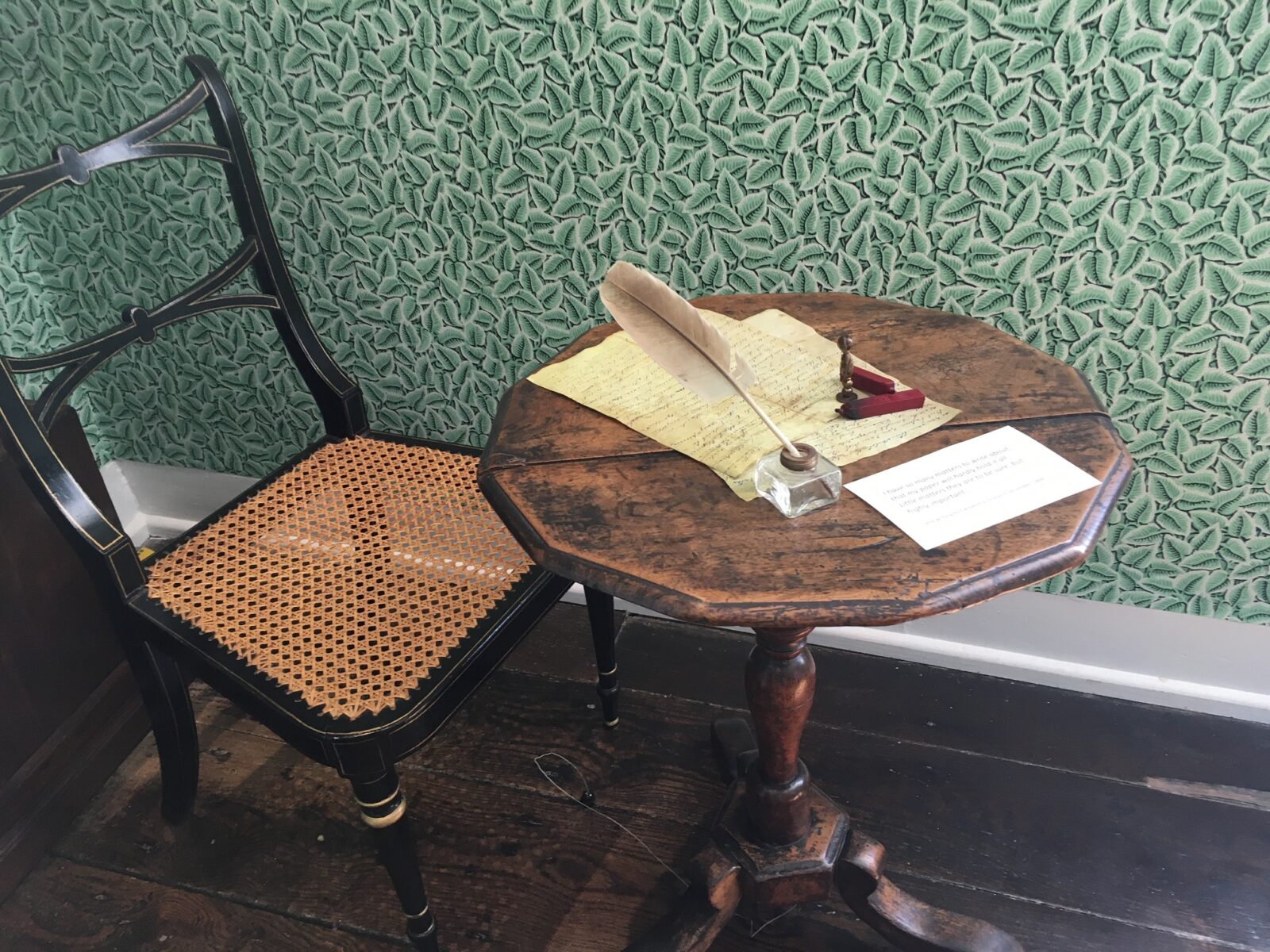 Jane Austen's small wooden writing table, with a facsimile letter and feather quill