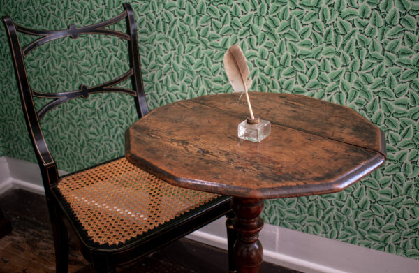 A small multi-sided writing table, belonging to Jane Austen with a quill in a glass ink stand on top. There is a cane seated chair and green wallpaper behind
