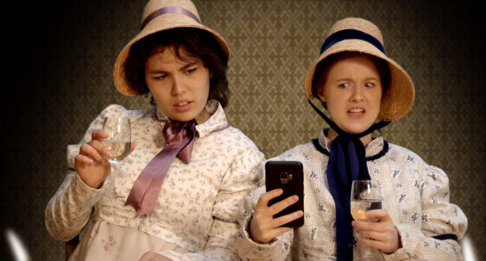 two girls in Regency dress look at a mobile phone in shock
