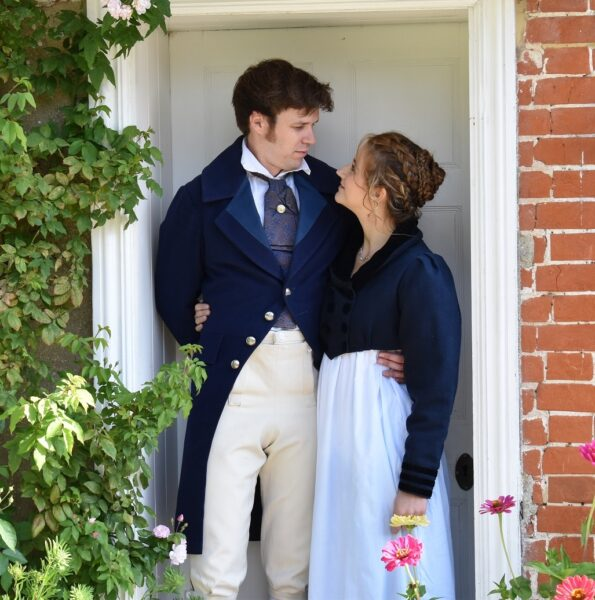 Actors portraying Captain Wentworth and Anne Ellliot from Persuasion standing in the doorway of Jane Austen's House