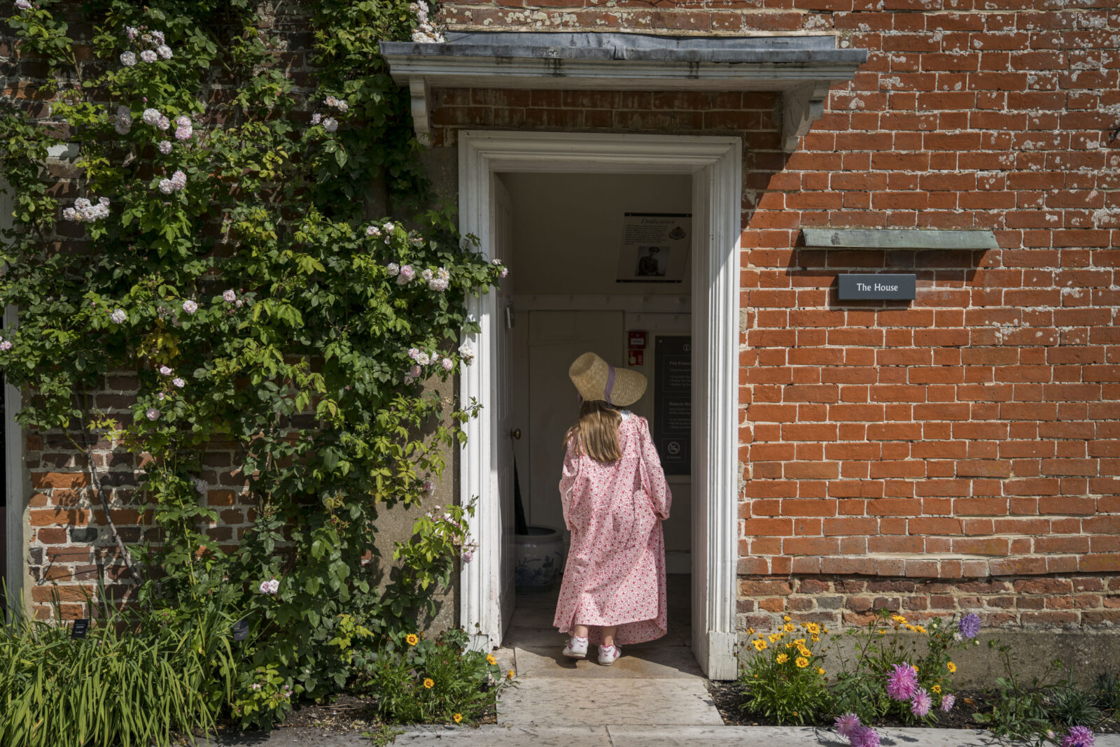 A young girl in a bonnet walking into Jane Austen's House