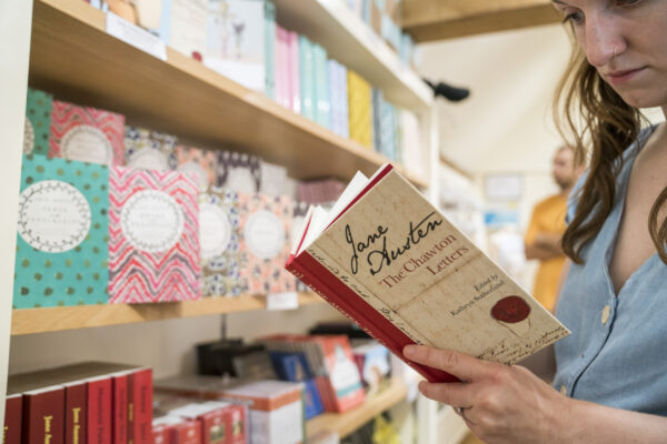 Woman looks at a book of Jane Austen's Chawton Letters in the shop at Jane Austen's House
