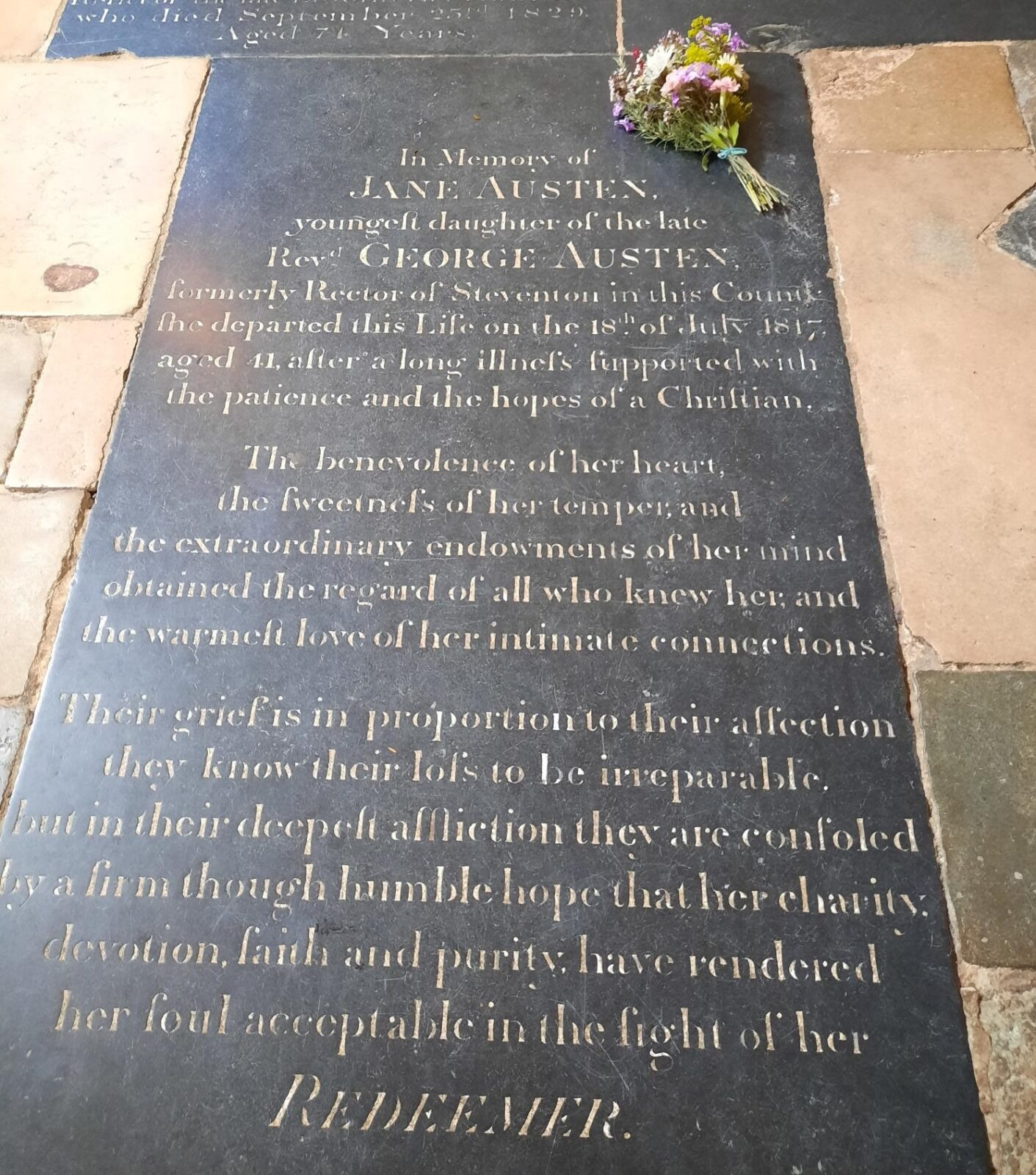 Jane Austen's gravestone in Winchester Cathedral, with a bunch of flowers laid on it