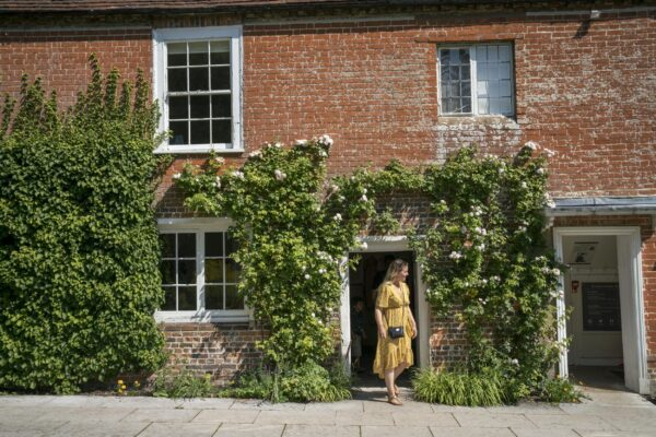 A woman in a yellow dress outside Jane Austen's House