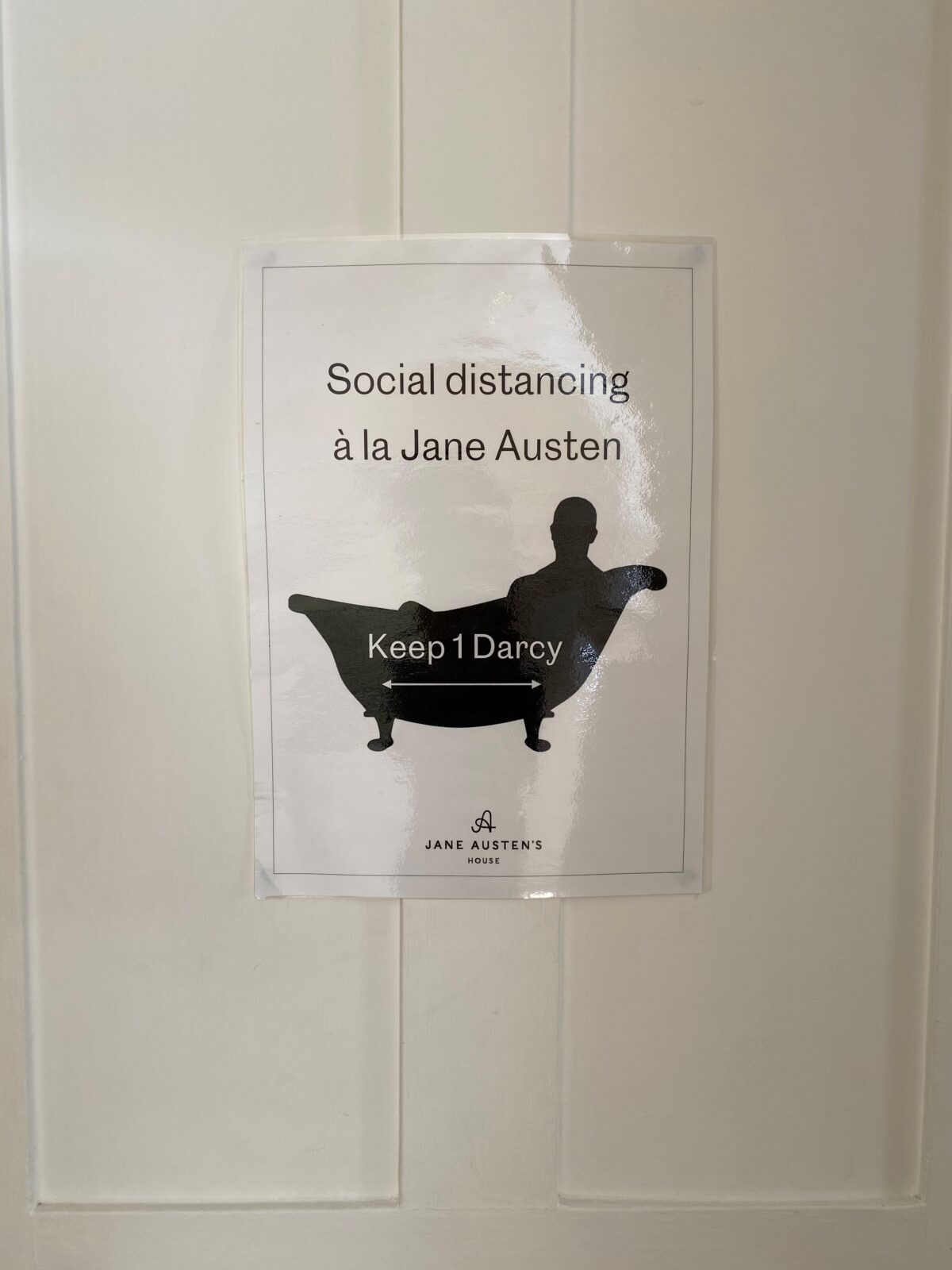 A sign that says 'Social distancing a la Jane Austen' above a silhouette of a figure in the bath