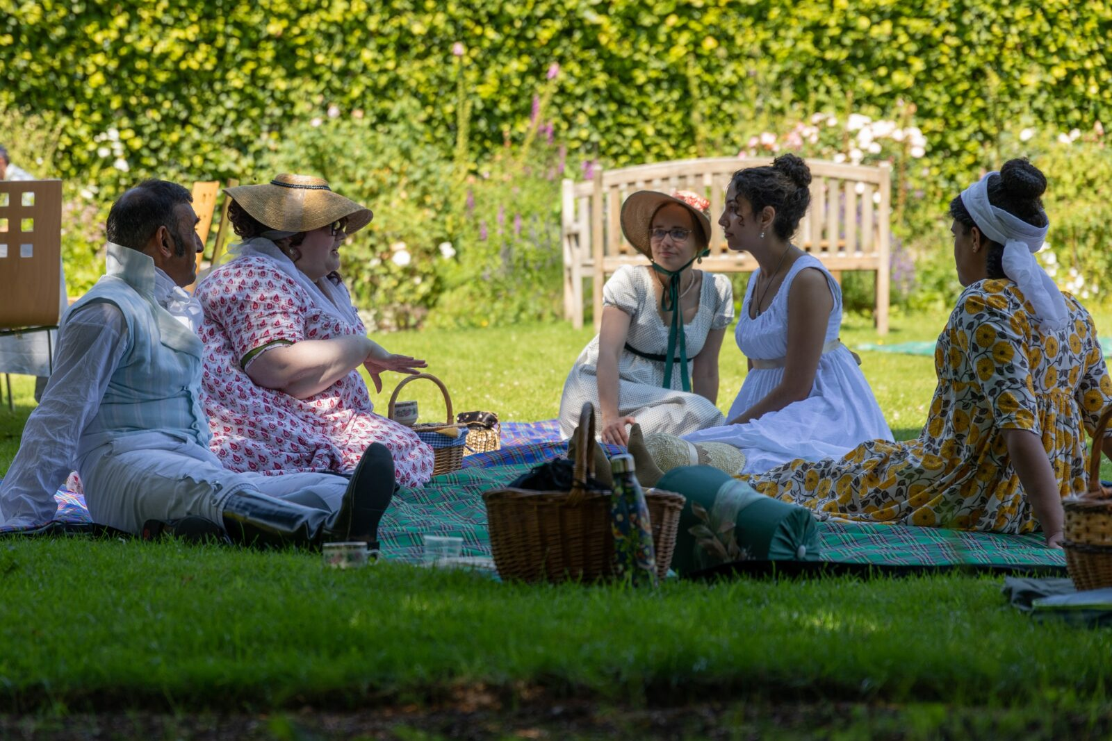 A group of men and women in Regency dress enjoying a picnic in the garden at Jane Austen's House
